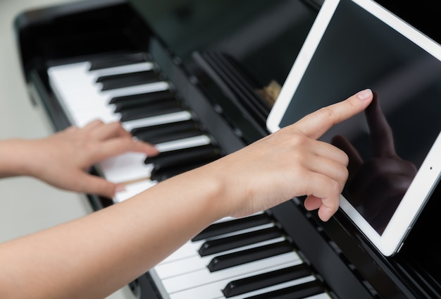 Woman with tablet learning to play the piano
