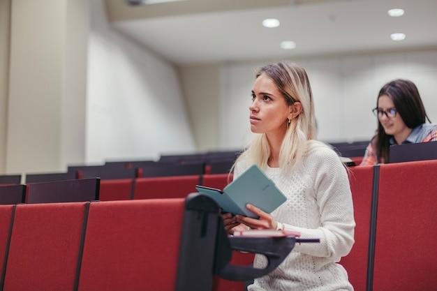 Женщина с таблеткой, слушающей лекцию