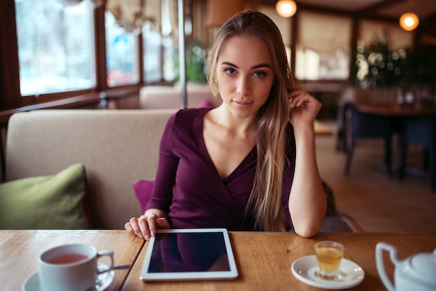 Woman with tablet pc using internet in restaurant.