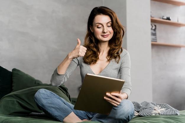 承認を示すタブレットを持つ女性