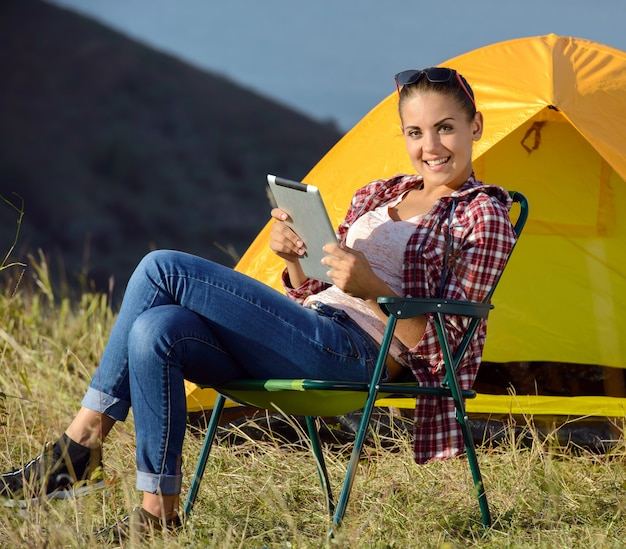 Woman with tablet sitting in chair. camping adventure