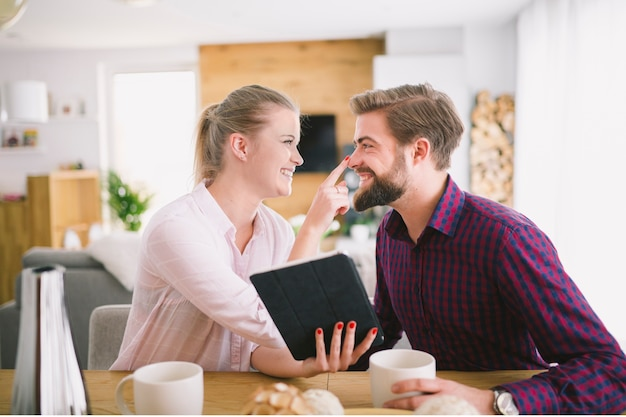 Woman with tablet touching boyfriend's nose