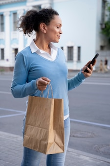路上でスマートフォンを使用して紙袋に持ち帰り用食品を持つ女性
