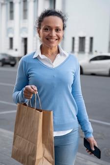 Donna con cibo da asporto in sacchetti di carta