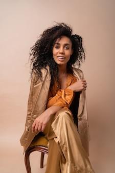 ヴィンテージの椅子ベージュの壁に座っているエレガントなオレンジ色のブラウスとシルクのズボンで完璧な巻き毛の黄褐色の肌を持つ女性。