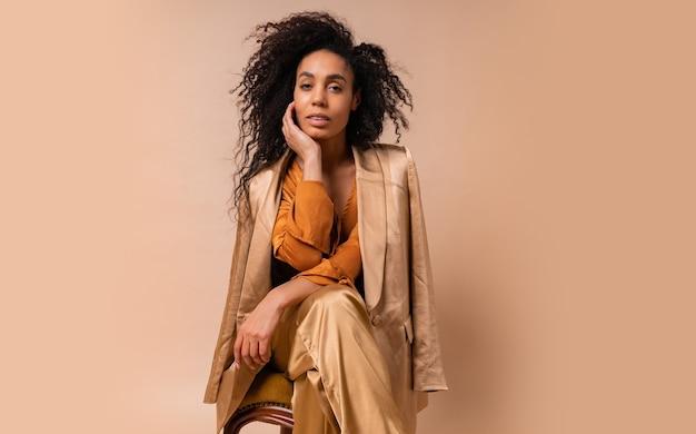 Женщина с загорелой кожей с идеальными вьющимися волосами в элегантной оранжевой блузке и шелковых брюках сидит на винтажном кресле у бежевой стены.