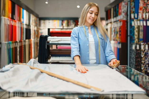 Женщина с рулеткой измеряет крупный план ткани в текстильном магазине. полка с тканью для шитья