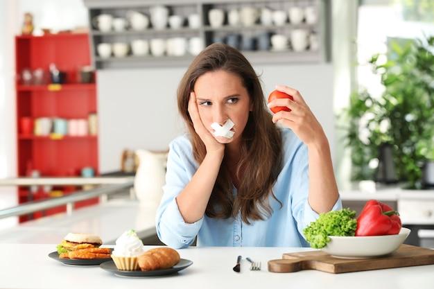 テープで留められた口と台所のさまざまな製品を持つ女性。健康食品と不健康食品の選択