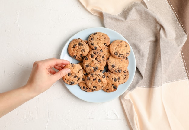 Woman with tasty chocolate chip cookies on gray background, top view.