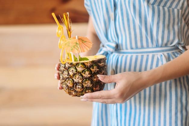 Женщина с вкусным коктейлем пина колада в ананасе, крупным планом