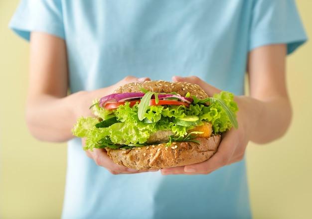 Женщина с вкусным веганским гамбургером, крупным планом
