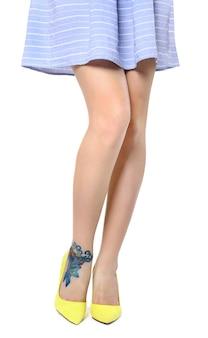흰색에 고립 된 높은 굽된 신발을 착용 그녀의 다리에 문신을 가진 여자