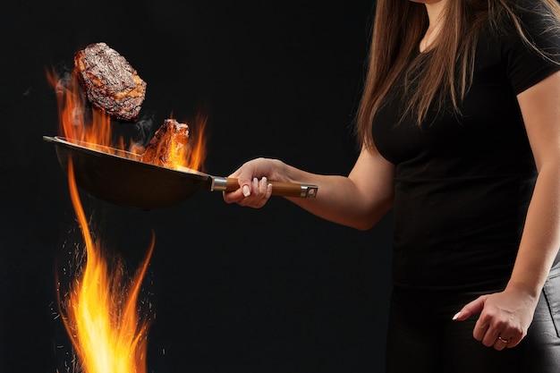 レギンスとtシャツに身を包んだ入れ墨のある女性が火と揚げ物の上に燃える中華鍋を持っています...