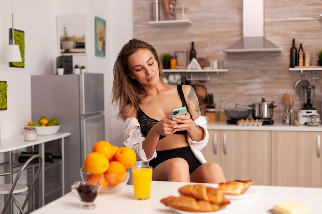 Woman with tattoos in sexy lingerie in home kitchen using smartphone. young seductive blode woman in seductive underwear with tattoos sitting in modern apartment.