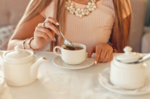 Женщина с чаем. руки держат чайную ложку. белая посуда на столе.