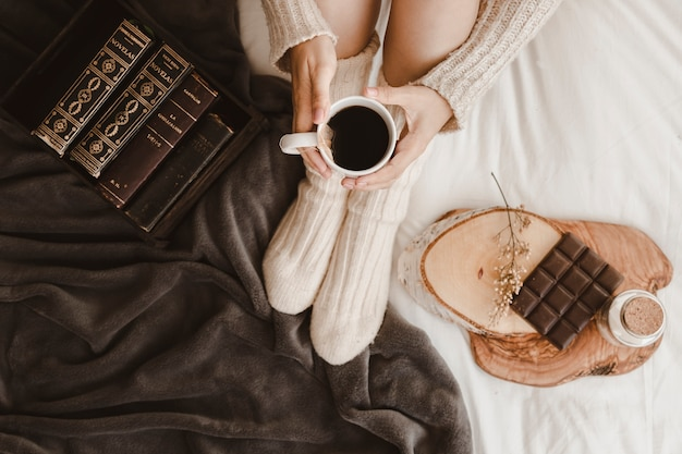 Woman with tea near books and chocolate