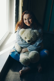 Woman with teddy bear by the window. girl looking out. concept oflife style, toys, holidays