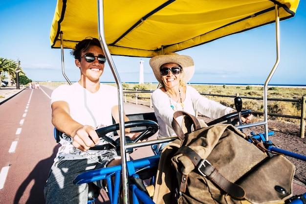 休暇中に道路でカートに乗って10代の息子を持つ女性。休日の余暇を楽しんでいる白人の母息子。幸せなママと息子が開いたカートを運転して楽しんでいます