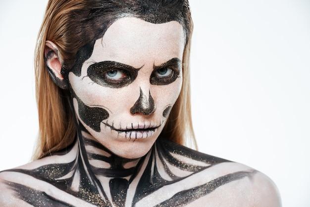 흰색 배경 위에 무서운 해골 화장을 한 여자