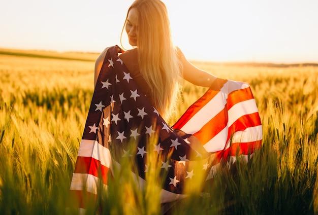 Женщина с американским флагом в пшеничном поле на закате