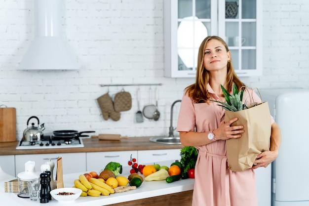 Женщина с пакетом продуктового магазина в руках. фон кухни. молодая женщина со здоровой пищей.
