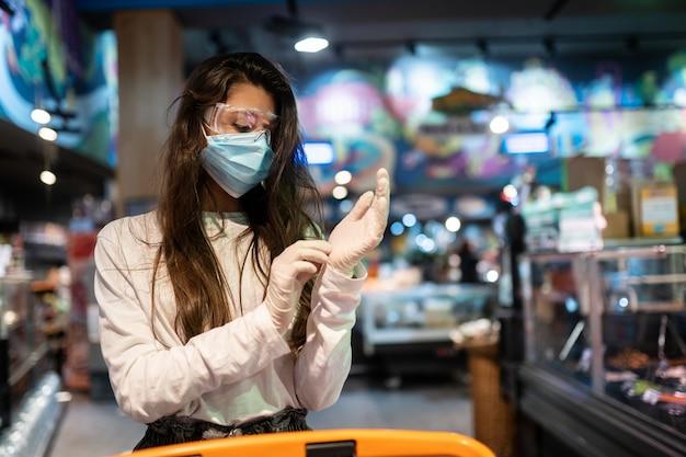 수술 마스크와 장갑을 가진 여자는 슈퍼마켓에서 쇼핑