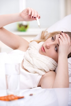Woman with thermometer has migraine in bed.