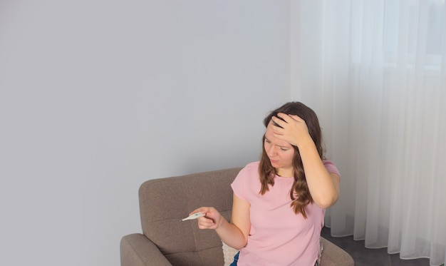Женщина с термометром больна простудой, гриппом, лихорадкой и мигренью в постели