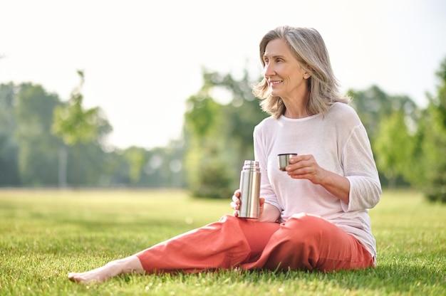 Женщина с термосом, сидя на траве в парке