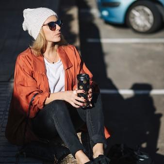 舗装の上に座る魔法瓶を持つ女性