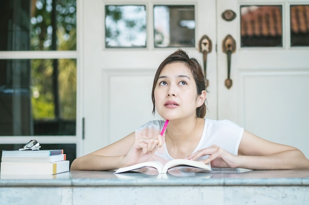 Woman with thinking face with a book on marble table