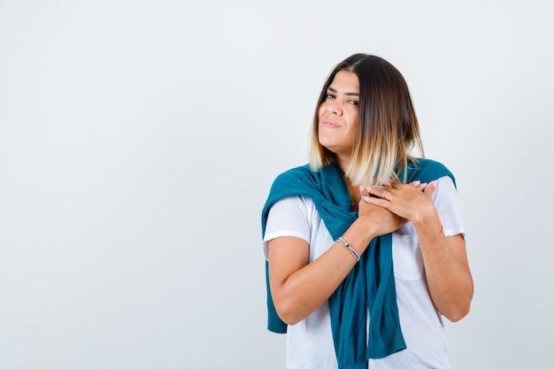 胸に手を保ち、感謝の気持ちを表す白いtシャツを着たセーターを結んだ女性。正面図。