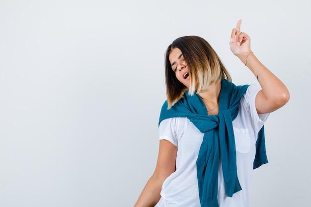 Donna con maglione legato in posa mentre punta verso l'alto in maglietta bianca e sembra energica. vista frontale.