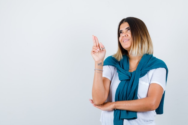 Woman with tied sweater showing gun gesture, looking up in white t-shirt and looking cheery. front view.