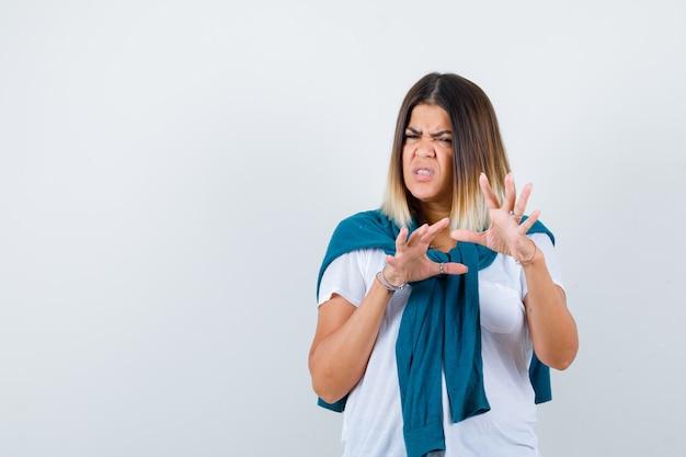 Donna con maglione legato che mostra il gesto di arresto in maglietta bianca e sembra disgustata. vista frontale.
