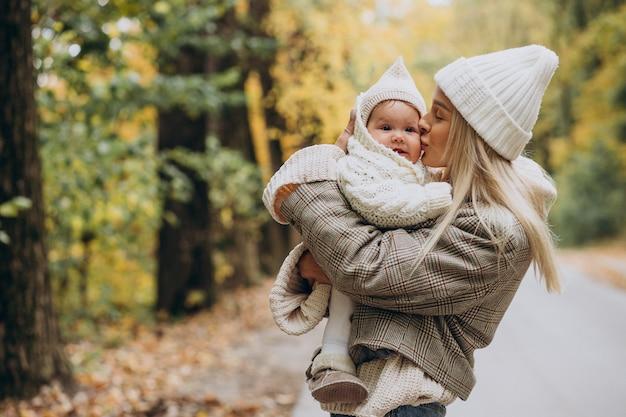 秋の公園で幼児の子供を持つ女性
