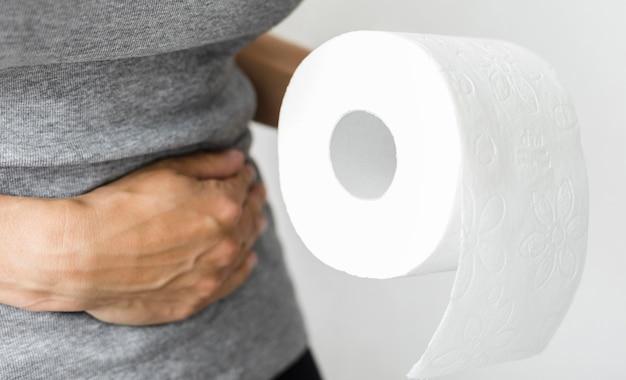 トイレットペーパーのロールを持つ女性