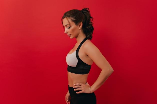 Donna con il corpo tonico che si esercita al fitness donna determinata durante l'allenamento fitness sulla parete isolata