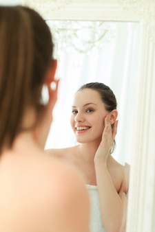 Woman with towel on body after shower, looking in mirror