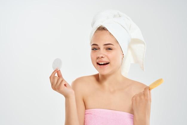 タオルを持った女性がスポンジの健康問題で肌をきれいにします衛生