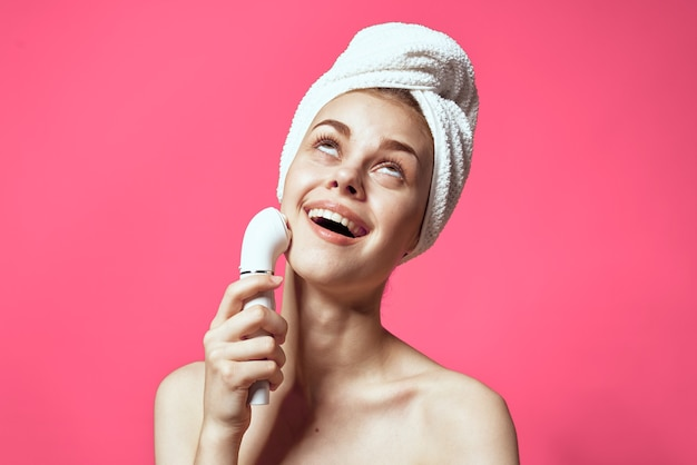 Woman with towel on head cleaning skin naked shoulders pink background