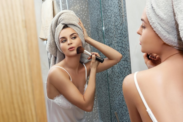 Woman with a towel on her head, looking in the mirror and applying make up