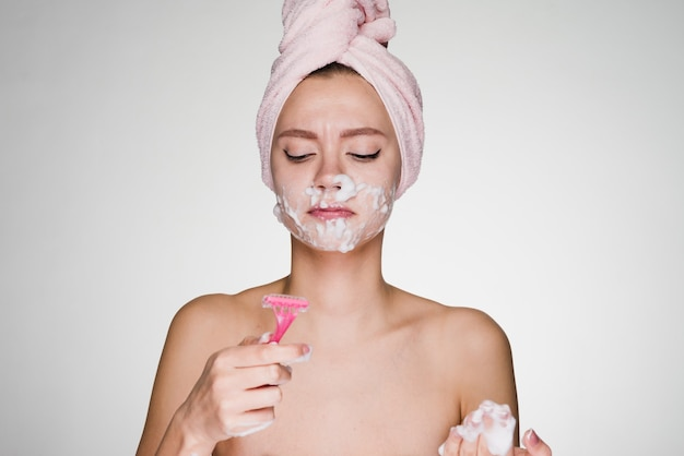 Woman with a towel on her head performs facial hair removal with a razor