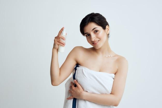 タオル裸の肩のローションときれいなスキンケアを持つ女性