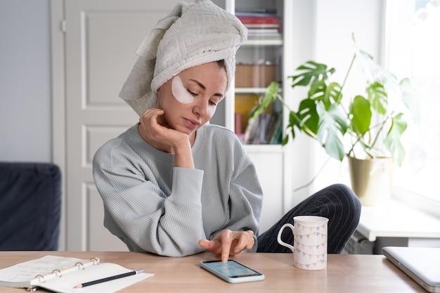 スマートフォンを使用して、ソーシャルネットワークフィードを読んで、頭にタオルと目の下にパッチを持っている女性