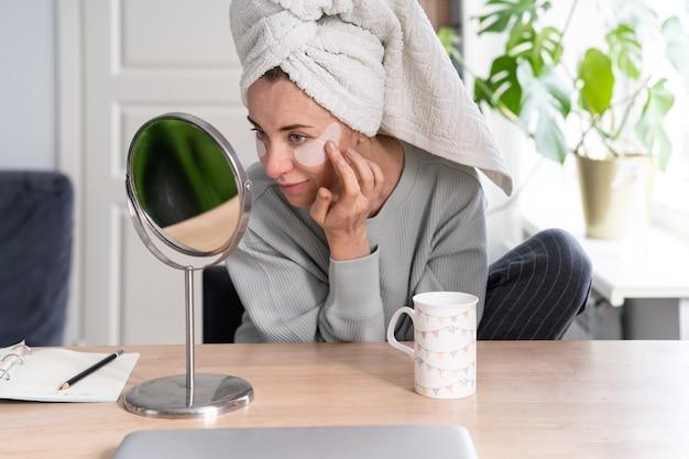 머리에 수건을 두른 여성은 집에서 거울을 보면서 하이드로 겔 눈 밑 회복 패치를 적용합니다.