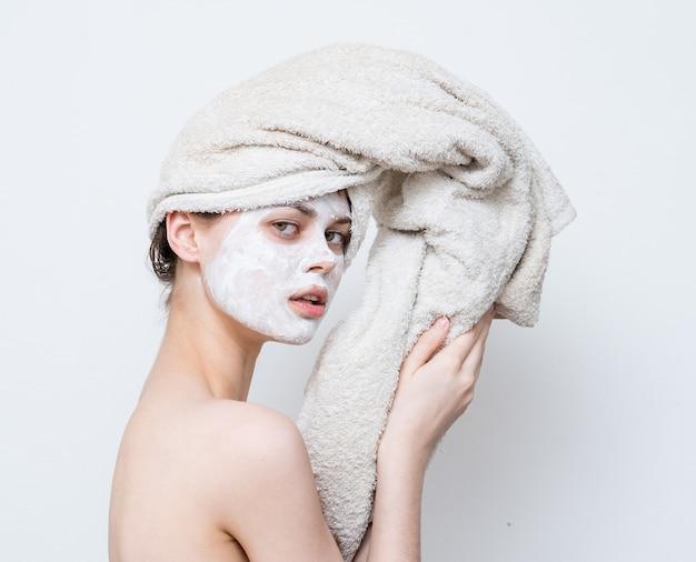 Женщина с полотенцем на голове, голые плечи, белая маска по уходу за кожей лица