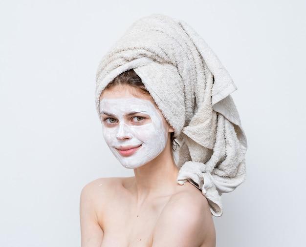 Женщина с полотенцем на голове, голые плечи, белая маска на уход за кожей лица.
