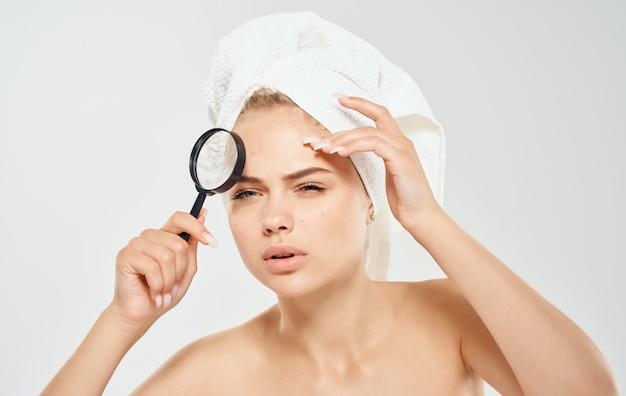 手に裸の肩の美容皮膚科の頭の拡大鏡にタオルを持った女性。