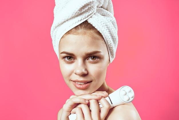頭にタオルを持った女性裸の肩スキンケア美容ピンクの背景
